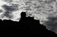 "Silhouette of Queribus Castle against a cloudy sky, Queribus Castle or Chateau de Queribus, Cathar Castle, Cucugnan, Corbieres, Aude, France. This castle, built from 13th to 16th centuries, is considered the last Cathar stronghold. It sits on a high peak at 728m. It is one of the ""Five Sons of Carcassonne"" or ""Cinq Fils de Carcassonne"". It is a listed monument historique and has been fully restored, restoration work being completed in 2002. Picture by Manuel Cohen"