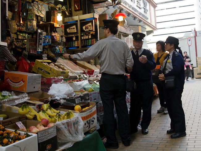 Hong Kong urban scene - police on partol stop at a street side shop