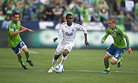 Vancouver Whitecaps FC  forward Gershon Koffie looks to pass while being pursued by Seattle Sounders FC midfielders Lamar Neagle, left, and Osvaldo Alonso  during play between the Seattle Sounders FC and the Vancouver Whitecaps FC at Qwest Field in Seattle Saturday June 11, 2011. The game ended in a 2-2 draw.