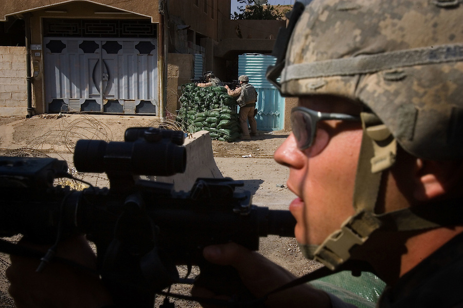 Soldiers from 1st Brigade 1st Armored Division take up positions behind sandbags as they pursue and investigate a car driven by a trio of insurgents in Ramadi, Iraq on Mon. Oct. 09, 2006.<br />