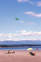 """People sunbathing and flying a Kite on the Beach at Qualicum Beach, in the """"Oceanside Region"""" of Vancouver Island, British Columbia, Canada"""