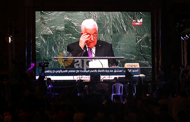 Palestinians watch a live-screening of president Mahmoud Abbas' speech followed by the raising of the Palestinian flag at the United Nations headquarters in New York, in the West Bank city of Nablus on September 30, 2015. Earlier in the week the UN General Assembly, by a two-thirds vote, adopted a resolution allowing the flags of Palestine and the Holy See ''both of which have non-member observer status'' to be hoisted alongside those of member states. Photo by Nedal Eshtayah