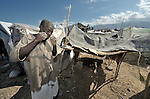A man uses his teeth to rip strips of cloth to fasten together a temporary shelter for his family in a spontaneous camp for quake survivors being established in Croix-des-Bouquets, Haiti, north of the capital Port-au-Prince. Quake survivors continue to move as aftershocks continue, and reports of aid deliveries in one camp will provoke families from other camps to migrate there.