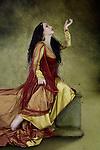 Beautiful Young Woman Sitting Posing looking up wearing long golden dress
