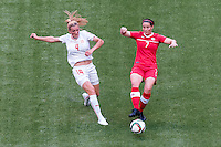 June 21, 2015: Rachel RINAST of Switzerland and Rhian WILKINSON of Canada compete for the ball during a round of 16 match between Canada and Switzerland at the FIFA Women's World Cup Canada 2015 at BC Place Stadium on 21 June 2015 in Vancouver, Canada. Canada won 1-0. Sydney Low/Asteriskimages.com