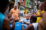 Men play cards near the entrance of Rocinha, in Rio de Janeiro, Brazil, on Friday, Feb. 1, 2013. The community of Rocinha, Latin America's largest favela with an unofficial population of about 250,000 residents. Pacification and police presence have made most of the area safer for both residents and visitors.