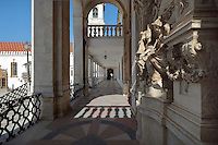 Allegorical sculptures along the facade of the Via Latina, in the portico of 1700-02 designed by Claude Laprade, 1682-1738, and a glimpse of the University clock tower, designed by Italian architect Antonio Canevari and built 1728-33, at the University of Coimbra in the former Palace of the Alcazaba, Coimbra, Portugal. The University of Coimbra was first founded in 1290 and moved to Coimbra in 1308 and to the royal palace in 1537. The buildings are listed as a historic monument and a UNESCO World Heritage Site. Picture by Manuel Cohen