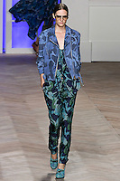 Sara Blomqvist walks the runway in a blue camouflage cotton motorcycle jacket, blue camouflage silk button-front tank top, and blue camouflage silk pleated trousers with ankle straps, by Tommy Hilfiger for the Tommy Hilfiger Spring 2012 Pop Prep Collection, during Mercedes-Benz Fashion Week Spring 2012.