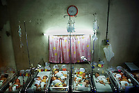 Multiple babies in single incubators in the maternity ward at Jose Fabella hospital.