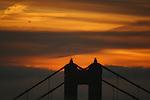 The sunrises over the Golden Gate Bridge as the fog runs into San Francisco Bay, California.