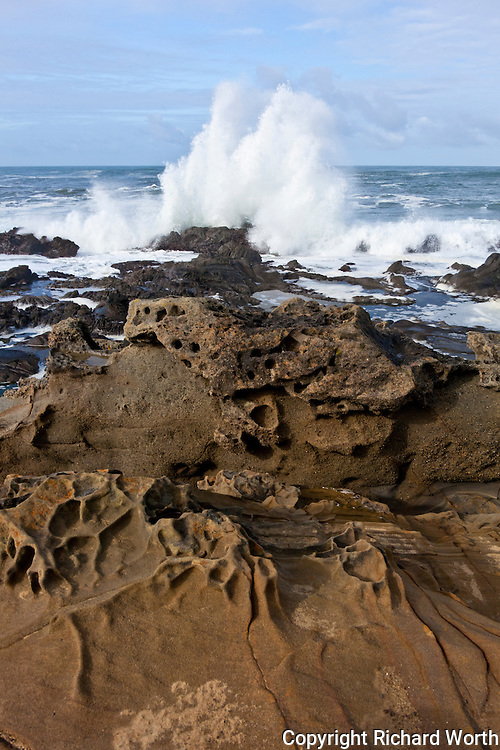 A wave crashes into and over  the rocks off Bean Hollow State Beach with a tofoni etched foreground.