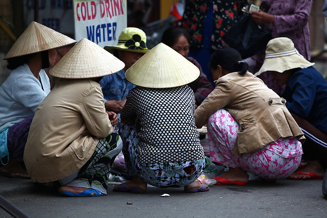 Women squat in a circle while doing business in the central market in Hoi An, Vietnam. April 22, 2012.