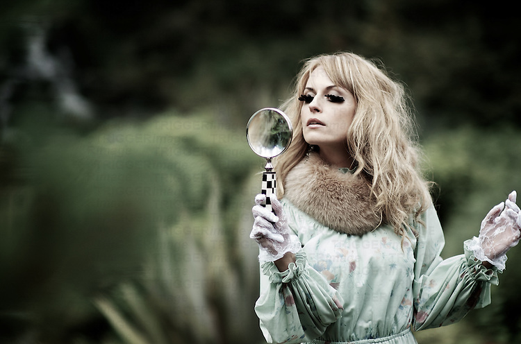 A young woman outside with long blonde hair wearing a period 70's dress and lace gloves holding a magnifying glass