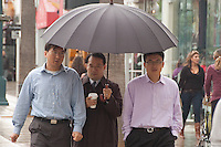 Three men share an umbrella at the Third Street Promenade on Tuesday, October 19, 2010.