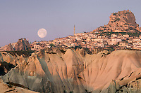 Uchisar, Cappadocia, Nevsehir, Turkey, May 2010. The full moon sets over the castle of Uchisar Village. The fairy landscape of Goreme National Park is unique in its kind. Millions of years long, wind and water sculpted the tuffstone into spectacular rock formations.  Photo by Frits Meyst / MeystPhoto.com