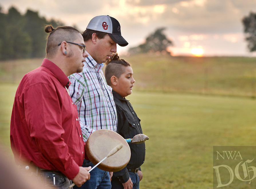 STAFF PHOTO BEN GOFF  @NWABenGoff -- 10/09/14 Ryan Mackey, from left, Howard Paden and Mackey's son Choogie Mackey, 11,  sing a traditional Cherokee song honoring bison prior to the release of 38 bison cows on Cherokee Nation tribal land in Eastern Oklahoma on Thursday October 9, 2014. The Cherokee Nation partnered with the Intertribal Buffalo Council to relocate the herd from Badlands National Park in South Dakota, and will add 10 bulls next week from Theodore Roosevelt National Park in North Dakota.
