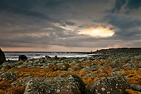 Stonebeach at Obrestad with lighthouse light at Nærland in the distance.