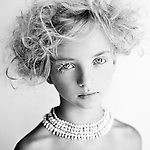 Close up of young girl wearing white mascara and necklace with hair up