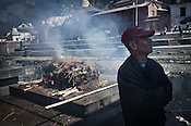 A family member breaks down while his family members' body burns on the pyre next to him outside the Pashupathi Nath Temple in capital Kathmandu, Nepal