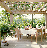 In the garden tall mature trees shade a table and chairs arranged on the wooden decking under a pergola