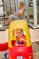 A woman sits in a patio chair outside her conservatory and breastfeeds her baby wilst her older child sits in a plastic ride-in car sipping a drink from a plastic cup through a straw.<br /> <br /> 09/07/2011<br /> Hampshire, England, UK
