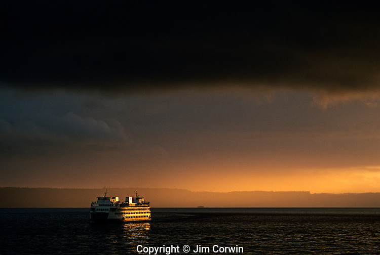 Ferry boat coming into the Edmonds ferry terminal sunset on Puget Sound with storm clouds Edmonds Washington State USA