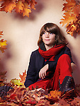 Boy wearing fall clothes, blue jacket with red pants and scarf, sitting on fallen red leaves, autumn childrens fashion artistic photo
