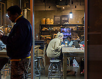 Customers take advantage of free wi-fi in the Bean & Bean Coffee shop in Chelsea in New York on Tuesday, November 17, 2015. The free wi-fi and the communal tables encourage the use of the coffee shop as a co-working space. (© Richard B. Levine)