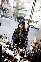 A young woman watching shop windows of luxury stores (Belgium, 05/11/2004)