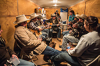Ranchers gather in a trailer on a cold night to play fiddles and banjos for entertainment on the range.