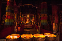 Buddhist Monk taken care of the Butter lamps,Inside old and ancient Monasteries Tibet
