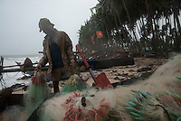 A fisherman organizes his nets after a night at sea on Mui Ne beach.