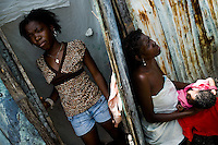 A young Haitian woman leaves the shack in the slum of Cité Soleil while her mother is taking care of her child, Port-au-Prince, Haiti, 24 July 2008. Cité Soleil is considered one of the worst slums in the Americas, most of its 300.000 residents live in extreme poverty. Children and single mothers predominate in the population. Social and living conditions in the slum are a human tragedy. There is no running water, no sewers and no electricity. Public services virtually do not exist - there are no stores, no hospitals or schools, no urban infrastructure. In spite of this fact, a rent must be payed even in all shacks made from rusty metal sheets. Infectious diseases are widely spread as garbage disposal does not exist in Cité Soleil. Violence is common, armed gangs operate throughout the slum.