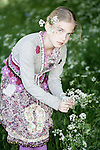 Close up of young girl with blonde hair wearing summer dress picking spring flowers outdoors in a garden