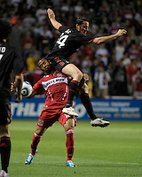 AC Milan defender Massimo Oddo lands on Chicago Fire midfielder Mike Banner (18) while attempting to play the ball.  AC Milan defeated the Chicago Fire 1-0 at Toyota Park in Bridgeview, IL on May 30, 2010.