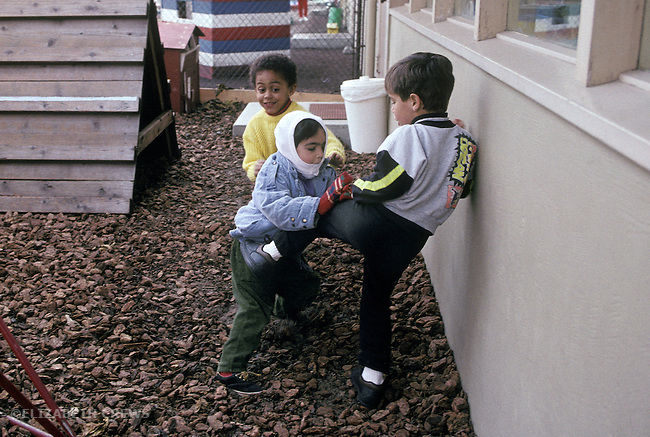 Palo Alto CA Boys, age four, involved in rough and tumble, rough-housing at preschool