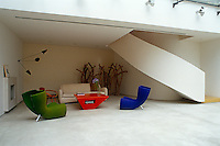 The seating area comprises a group of coloured furniture and is located in the lee of a curved staircase