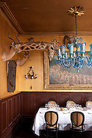 """The walls of the restaurant, which doubles as a dining room for the trio, is decorated with the head of a giraffe from London Zoo and a 1900 canvas entitled, """"Le fleuve de la vie"""" by Belgian artist Lucien Foller"""