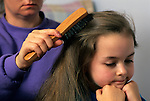 Early morning before school mother combing daughters ( 6 years old) hair with girl bored Marysville Washington State USA  MR