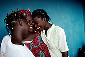 Freetown, Sierra Leone<br /> April 2001<br /> <br /> Jalikaou Tity Turay, 18 (right) and her sister N'yillah Turay (left), 16 are reunited with their mother Yeabu Turay in Freetown, Sierra Leone after 3 years in Guinea as war refugees.