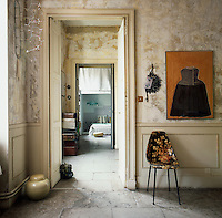 The apartment has a rustic feel, with a distressed finish on the walls and a flagstone floor. A view through an open doorway leads to a bedroom beyond