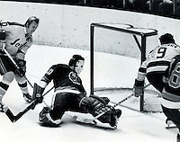 Seals action, #9 Ivan Boldirev sticks the puck under Gerry Desjardins of the Islanders as Stan Gilbertson comes in on the left. (photo by Ron Riesterer)