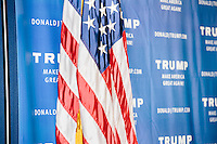 An American flag stands in front of Trump posters as real estate mogul and Republican presidential candidate Donald Trump speaks to supporters at a rally at the Weirs Beach Community Center in Laconia, New Hampshire.