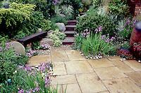 Stone patio, rustic wood bench, steps, irises. Design: Geoffrey Whiten. spring garden landscaping, shrubs, flowers, perennials
