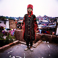 Nine year old Tarveena the Magician wears her performance dress on a rooftop overlooking the Kathputli Colony. Located in northwest Delhi, Kathputli is inhabited by approximately 2,000 performing artists, practicing traditional art forms such as marionette puppetry, juggling, magic, acrobatics, dance and music. Many have travelled all over the world showcasing their abilities, but they still choose to remain living in this slum, which is one of the most impoverished in the city.