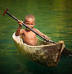 Young boy paddling a dugout canoe, Lobo Village, Papua