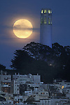 The full moon rises behind Coit Tower, San Francisco, CA.