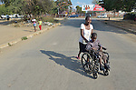 Eric Lovemore, 8, gets pushed along a street in Bulawayo, Zimbabwe, by his stepmother, Zandile Tohori. Lovemore suffered cerebral palsy and uses a wheelchair provided by the Jairos Jiri Association with support from CBM-US. Tohori is pushing the boy home from school.