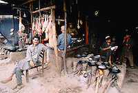 A Pakistani butcher next to a Afghan restaurant in Peshawar, Pakistan