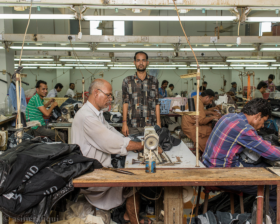 Leather jacket manufacturing and stitching work shop. Workers sew the various pieces to complete the customer's order.